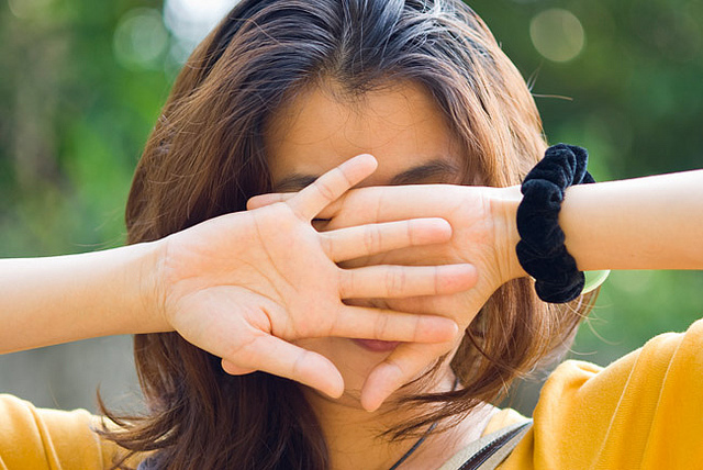 Young woman use hands covered her face