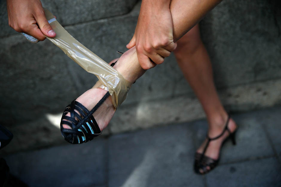A man puts on his high heel shoes before the annual race on high heels during Gay Pride celebrations in the quarter of Chueca